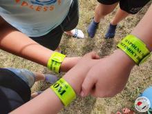 Opaski odblaskowe na rękach dzieci z hasłami propagującymi przeciwdziałanie przemocy