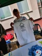 pracownik socjalny prezentujący koszulkę z hasłami przeciwdziałającymi przemocy