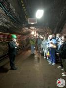 Grupa seniorów wraz z przewodnikiem w korytarzu kopalni