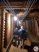 Seniorzy idą podziemnym korytarzem